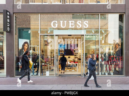 View of Guess luxury fashion house store entrance with brand signage and people passing by in The Hague, Net - Stock Photo