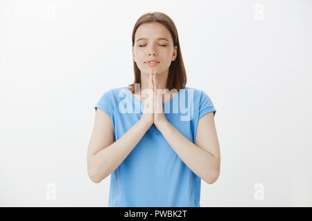 Namaste, need to calm down and breathe. Portrait of relaxed attractive happy european woman in blue t-shirt, holding palms clenched in pray, closing eyes, meditating or practising yoga - Stock Photo