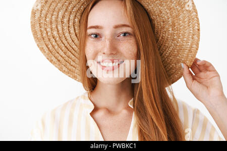 Headshot of happy charming redhead girl enjoying vacation smiling broadly at camera holding straw hat on head and gazing at camera with friendly delighted expression over white background - Stock Photo