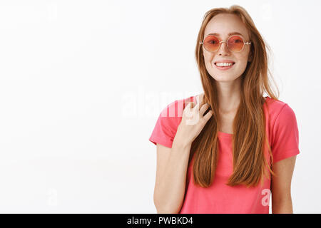 Studio shot of cute happy and emotive young redhead female in pink sunglasses and t-shirt touching strand of hair and smiling feeling awkward in unfamiliar company trying start conversation friendly - Stock Photo