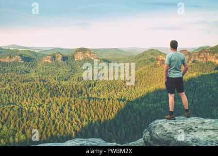 Tall man in outdoor clothes stands alone on the peak of rock. Hiker watching hilly forest landsape in morning mist. - Stock Photo