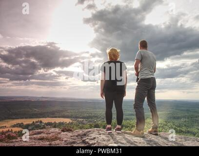 Back view of young tourist couple, athletic man and girl stand  on rocky mountain top enjoying breathtaking mountain view - Stock Photo