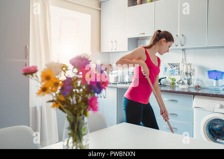 Young woman washing floor with mop in modern kitchen decorated with flowers. Household chores - Stock Photo