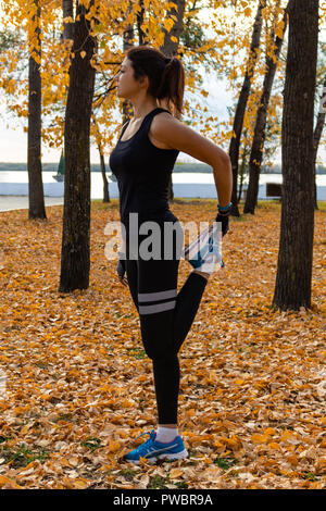 Young sportswoman stretching and preparing to run. - Stock Photo