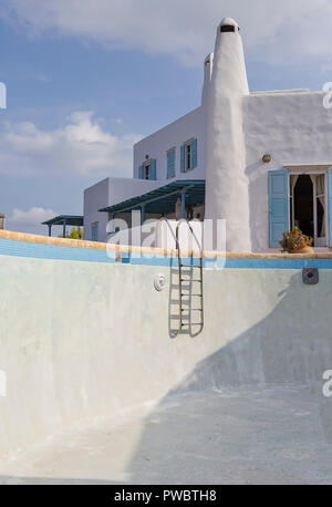 Empty Swimming Pool. A typical Cycladic Architecture  of a Greek Island house  in the background. - Stock Photo