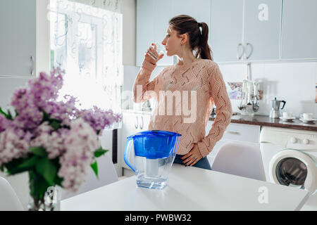 Woman drinking filtered water from filter jug in kitchen. Modern kitchen design. Healthy lifestyle concept. - Stock Photo