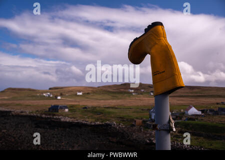 A Yellow rubber boot put on a metal post pillar, Isle of Skye, Scotland, Uk - Stock Photo