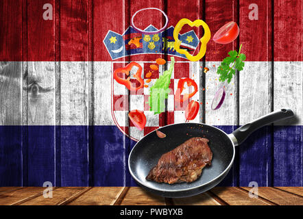 Cooking process. Hot movement. Fresh vegetables falling into the pan with meat, cooking concept on wooden flag background of Croatia - Stock Photo