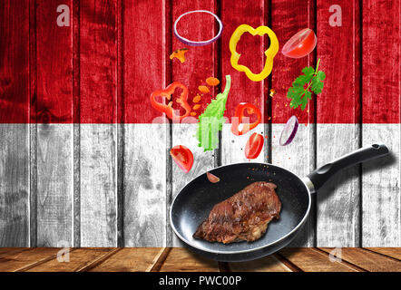 Cooking process. Hot movement. Fresh vegetables falling into the pan with meat, cooking concept on wooden flag background of Monaco - Stock Photo