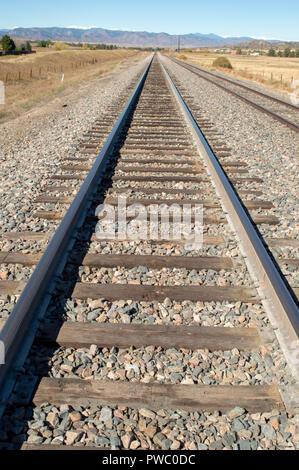 Empty Colorado railroad track leading to the Rocky Mountains through Castle Rock - Stock Photo
