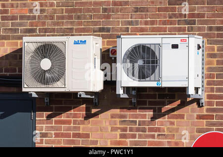 Pair of small commercial air condensing refrigeration units for shop air conditioning mounted on an outside wall in the UK. - Stock Photo