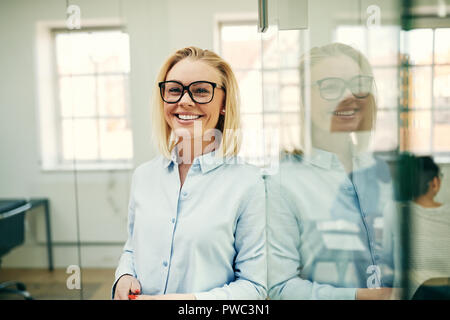 Young businesswoman smiling confidently while leaning against a glass wall in an office with colleagues in the background - Stock Photo