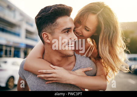 Smiling young man giving his laughing girlfriend a piggyback while walking together down a street in the city - Stock Photo