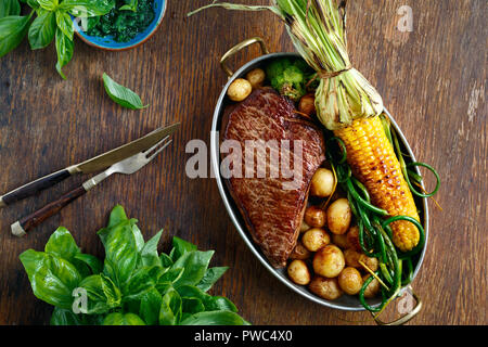Beef steak served in frying pan with fried corn, potatoes and green beans on wooden table, top view - Stock Photo