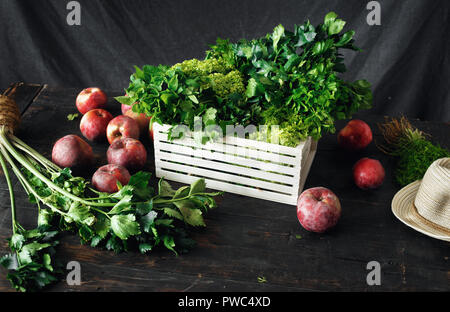Freshly picked herbs and apples in wooden box harvesting concept - Stock Photo