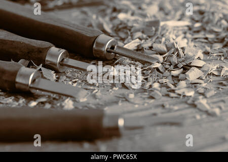 Chisels on a wood background with shavings - Stock Photo