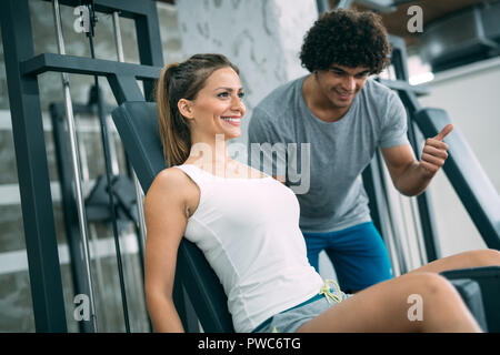 Personal trainer helping young woman reach goals - Stock Photo