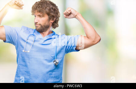 Handsome hispanic surgeon doctor man over isolated background showing arms muscles smiling proud. Fitness concept. - Stock Photo