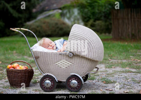 Little newborn baby boy, sleeping in old retro stroller in forest, autumn time. Posed baby in retro pram, baby sleeping, vintage stroller - Stock Photo