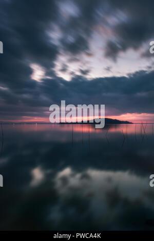 Sunset over Trasimeno Lake, cloudy day. Mirror like reflection. Italian landscape. - Stock Photo