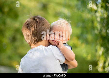 Little toddler baby boy, crying, older brother carrying him in the park, baby looking at camera - Stock Photo
