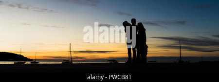 Rear view of silhouetted family outdoors  hugging looking at the sunset with the sea, mountain and sailboats behind in a wide panoramic view against e - Stock Photo