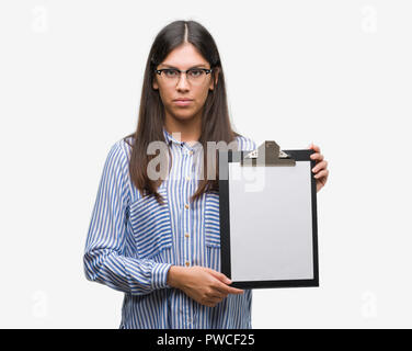 Young hispanic woman holding clipboard with a confident expression on smart face thinking serious - Stock Photo