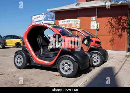 Close-up of two VELSAR - (Sardinia Electric Vehicles) Renault TWIZY  two-seat electric vehicles for hire in Alghero, Sardinia, Italy - Stock Photo
