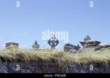 Celtic crosses appear over a grassy stone wall on a windy day with blue sky in this Irish landscape - Stock Photo
