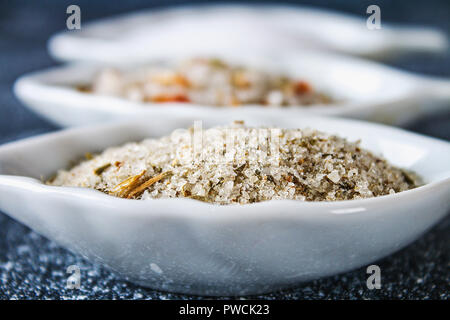 Different types of salt in glass bowls on a dark gray table. Background for advertising salt. Table salty. Salted food - Stock Photo