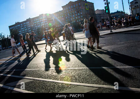 Russia, Moscow - 10 July 2018: Anonymous people with long shadow on zebra crossing - Stock Photo