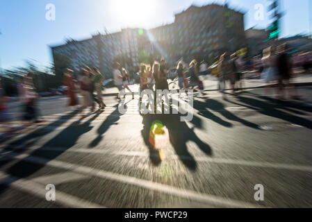 Crowd of blurred anonymous people with long shadow walking on zebra crossing. Zoom effect - Stock Photo
