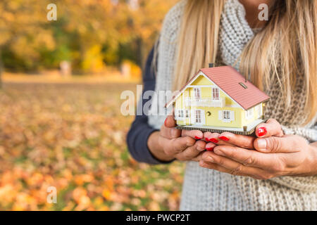 Young loving couple holding small model house in autumn garden or park - Stock Photo
