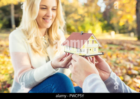 Young loving couple holding small model house in autumn garden or park. - Stock Photo