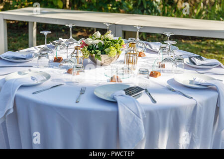 Set table for a white wedding dinner decorated with flowers. Concept of tropical wedding. - Stock Photo