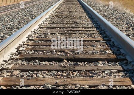 Closeup of Colorado railroad track leading into the distance - Stock Photo