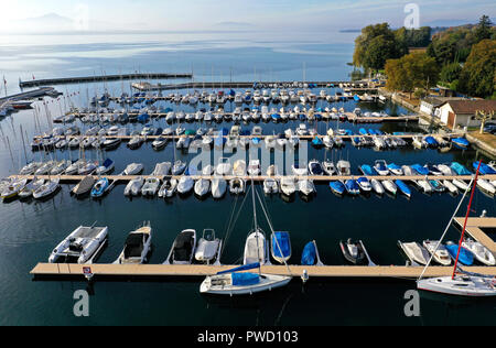 Boats moored at berths in a yacht harbour at the Lake Geneva, Rolle, Vaud, Switzerland - Stock Photo