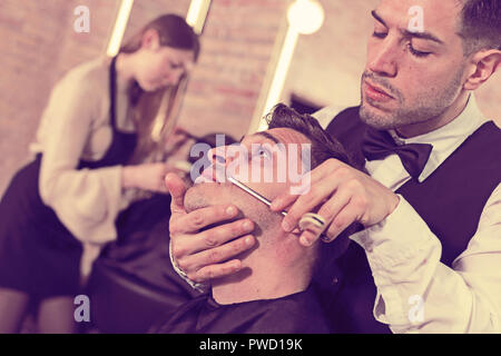 Male client getting old-fashioned shave with straight razor from male barber in modern salon - Stock Photo