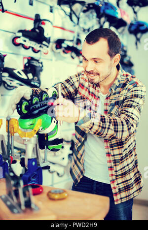 Satisfied pleasant smiling male repairer fixing roller-skates in sports store - Stock Photo