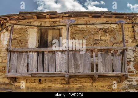 Old vintage run-down wooden balcony, stone facade - Stock Photo