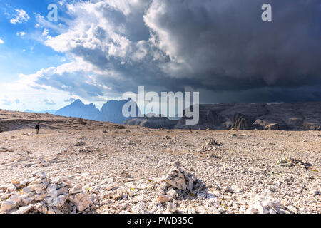 A tourist walk on the Piz Pordoi with coming storm in the background. Fassa Valley, Trentino, Dolomites, Italy, Europe. - Stock Photo
