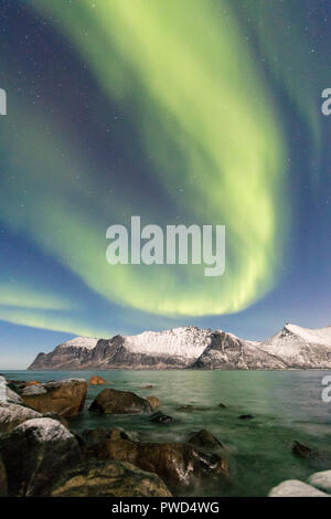 Northern lights on snowy peaks and icy sea along Mefjorden seen from the village of Mefjordvaer Senja Tromsø Norway Europe - Stock Photo
