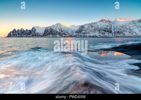 The waves of the icy sea crashing on the rocky cliffs at dawn Tungeneset Senja Troms county Norway Europe - Stock Photo