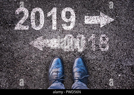 2019 and an arrow written on an asphalt road background with legs - Stock Photo