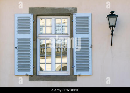 reflection of a historical building in an old wooden, blue window on a white wall - Stock Photo
