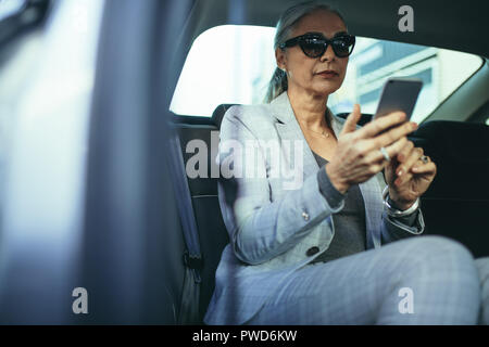 Stylish mature woman sitting on backseat of her car reading text message on mobile phone. Senior businesswoman traveling by a car using smart phone. - Stock Photo
