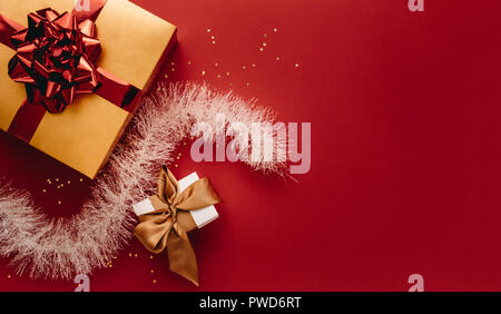 Gift boxes in different sizes with stars and garland with copy space. Flat lay of christmas gifts and decorations on red backdrop. - Stock Photo