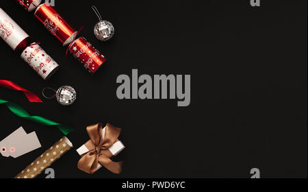 Christmas decoration flat lay on black background. Directly above shot of christmas crackers, mirror balls, colorful ribbons, tags and gift box with c - Stock Photo