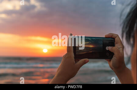 Girl takes pictures on smartphone dawn on the sea - Stock Photo