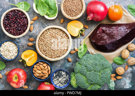 Foods high in iron. liver, broccoli, persimmon, apples, nuts, legumes, spinach, pomegranate. Top view, flat lay - Stock Photo